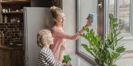 Happy mother and daughter cleaning window